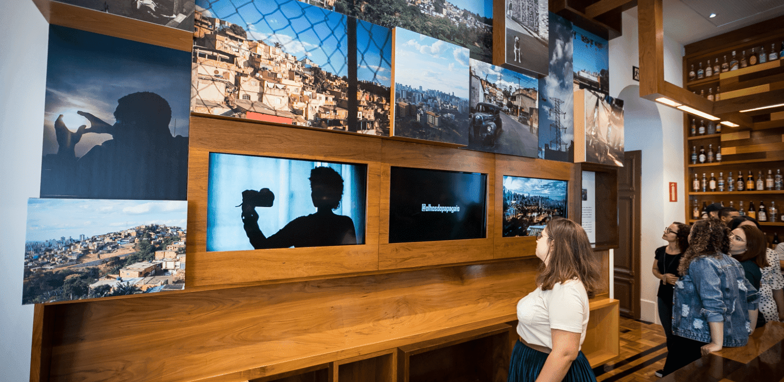 Woman watching videos on a wall with televisions and various pictures